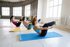 Women doing abdominal crunches at group workout royalty free stock photography