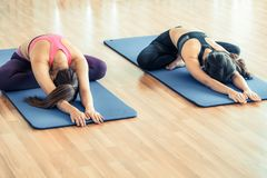 Women doing back stretching yoga in fitness gym Stock Photo