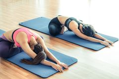 Women doing back stretching yoga in fitness gym Stock Images