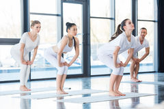 Women doing chair pose utkatasana. With instructor indoors Royalty Free Stock Photo