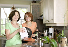 Women doing dishes in kitchen Royalty Free Stock Images