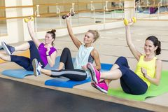 Women doing dumbbell exercises at a group workout in a fitness room stock photo