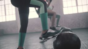 Women doing exercise with medicine ball in gym. Young women exercising in aerobics class with medicine balls on floor. Three females doing exercise with medicine