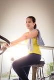 Women doing indoor biking in a fitness club. Happy woman doing indoor biking in a fitness club Stock Photo