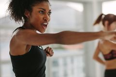 Women doing intense punching work out at the gym. African young women doing intense punching work out at the gym. Young slim women in sportswear doing exercise Stock Photos
