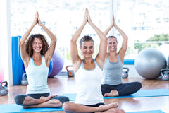 Women doing lotus pose with hands joined overhead Royalty Free Stock Photo
