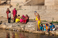 Women doing pooja in Rajasthan. JAISALMER, RAJASTHAN, INDIA - MARCH 13, 2015: Women in colorful saris doing pooja religious ritual near Gadi Sagar saint lake Royalty Free Stock Photo