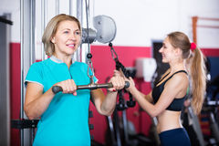 Women doing powerlifting on machines. Portrait of happy elderly and young women doing powerlifting on machines in jym Royalty Free Stock Images