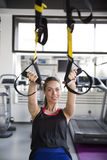 Women doing push ups training arms with trx fitness straps. In the gym Stock Photography