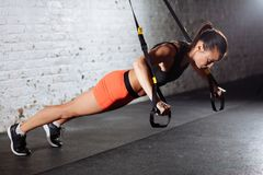 Women doing push ups training arms with trx straps in gym royalty free stock images