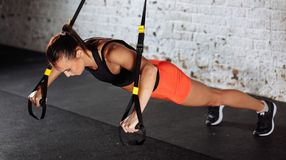 Women doing push ups training arms with trx straps in gym. Women doing push ups training arms with trx fitness straps in gym royalty free stock photos
