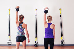 Women doing shoulder press with kettlebells Royalty Free Stock Photos