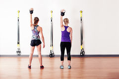 Women doing shoulder press with kettlebells Royalty Free Stock Image