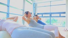 Women doing sit ups on exercise balls Stock Photo