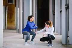 Women doing squat exercise workout. Two fitness women doing squat exercise workout outdoor. Female coach correcting knee position for legs exercising Royalty Free Stock Images