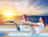 Women doing yoga half-boat pose outdoors. Fitness, sport, people and healthy lifestyle concept - women doing yoga half-boat pose on mat outdoors on wooden pier Royalty Free Stock Photo