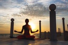 Woman doing yoga at sunrise near the sea. The women doing yoga at sunrise near the sea Royalty Free Stock Image