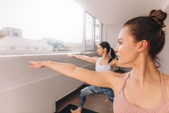 Women doing yoga in warrior pose at studio Stock Image