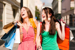 Women downtown shopping with bags Stock Images