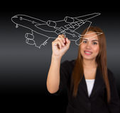 Women are drawing the plane on white board. Royalty Free Stock Images