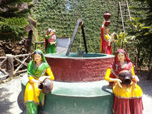 Women drawing water from a well. Colorful depiction of women drawing and carrying water from a well at Sahastradhara Heights, a family fun destination near Stock Photography