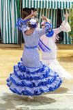 Women dressed in colourful flamenco dresses and dancing at the Seville April Fair. royalty free stock image
