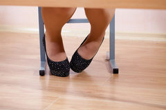 Women dressed in shoes under the table Stock Photo