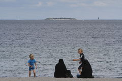 Women dressed in traditional Islamic dress on beach. COPENHAGEN, DENMARK - July 28, 2016: Women dressed in traditional Islamic dress were seen walking at Royalty Free Stock Photos