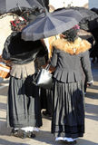 Women dressed in vintage clothes and a black umbrella to protect stock photos