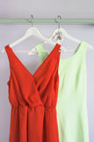 Women dresses. Bright and vibrant colored women clothes hanging on a wooden board stock photography