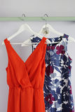 Women dresses. Bright and vibrant colored women clothes hanging on a wooden board royalty free stock photos