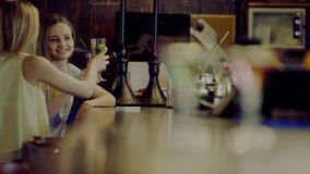 Women drink cocktails. Two beautiful young smiling women clinking glasses and drinking cocktails sitting at a bar counter stock footage
