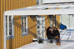 Women drink coffee in front of the old wooden house in Tromso, Norway. Royalty Free Stock Images