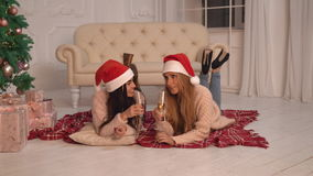 Women drinking champagne near christmas tree at home stock video footage