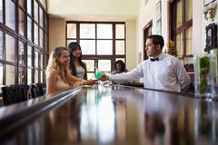 Women drinking cocktail in pub. Female friends sitting in pub and hispanic barman serving cocktail. Horizontal shape side view, copy space Stock Photography