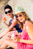 Women drinking cocktails at beach Royalty Free Stock Photo