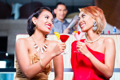 Women drinking cocktails in fancy bar. Asian women drinking cocktails in fancy bar Royalty Free Stock Photos