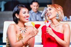 Women drinking cocktails in fancy bar. Asian women drinking cocktails in fancy bar royalty free stock photography