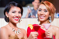 Women drinking cocktails in fancy bar. Asian women drinking cocktails in fancy bar Royalty Free Stock Images