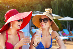 Women drinking a cocktails while relaxing by the swimming pool Stock Photo