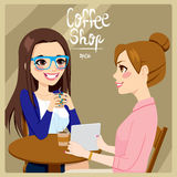 Women Drinking Coffee. Two young women friends drinking coffee and enjoying relaxing time talking while watching a tablet computer Royalty Free Stock Photography