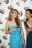Women Drinking Martinis Against Floral Print Wall Stock Images