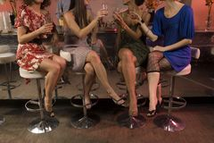 4 women drinking at a mirrored bar, raising their glasses, cropped, focus on bodies Stock Photos