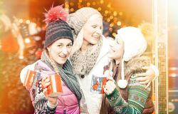 Women drinking mulled wine in mugs on German Christmas Market Royalty Free Stock Image