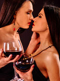 Women drinking red wine on nightclub. Lesbian women drinking red wine and kissing on nightclub Stock Image