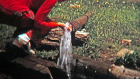 1972: Women drinking well drawn water from the end of a pipe. stock video