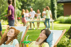Women with drinks sunbathing. During casual garden party Stock Images