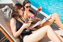 Women with drinks by swimming pool Royalty Free Stock Photos