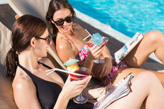 Women with drinks by swimming pool Stock Images