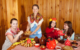 Women  drinks tea and eats pancakes Stock Images